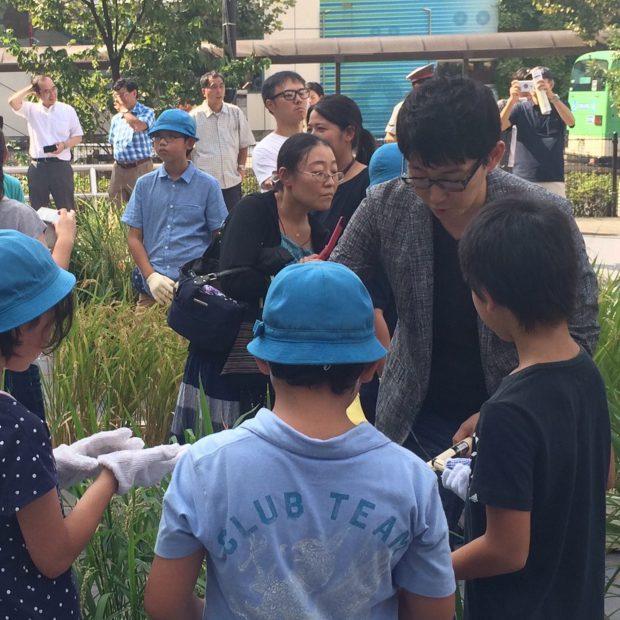 子ども達に稲刈りの仕方を教える代表の中村祐介